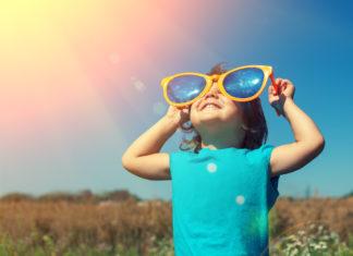 Kind met grote zonnebril kijkt naar de zon
