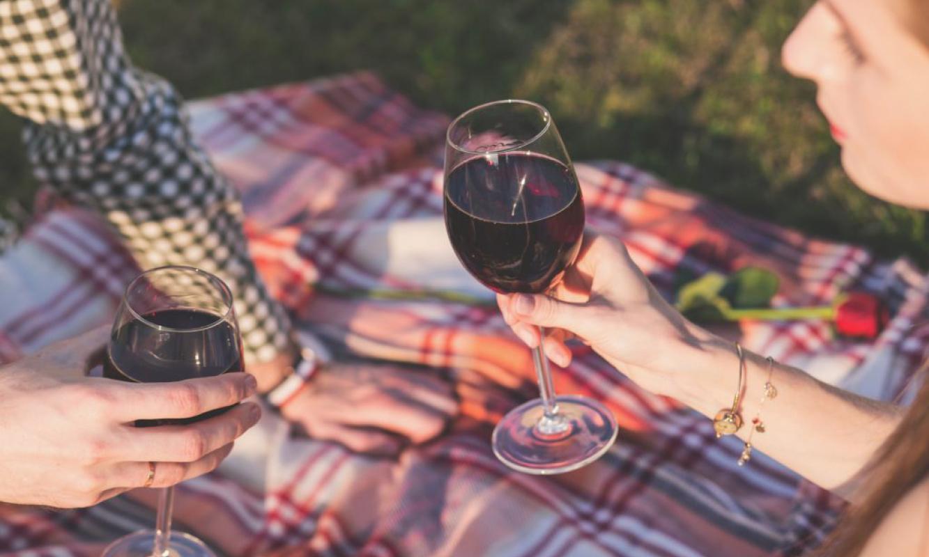 Romantisch koppeltje op deken met rode wijn