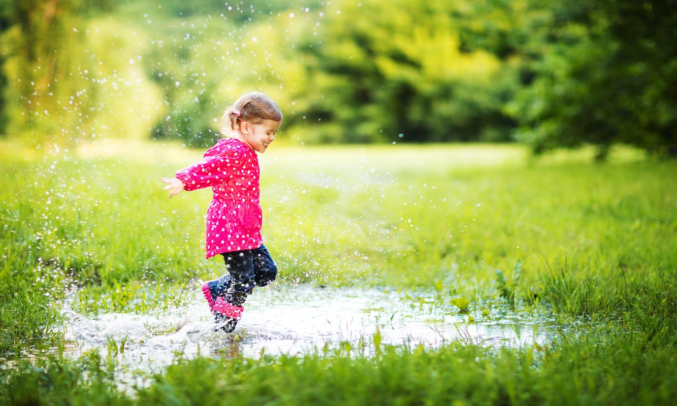 Kindje speelt in regenplas in het groen